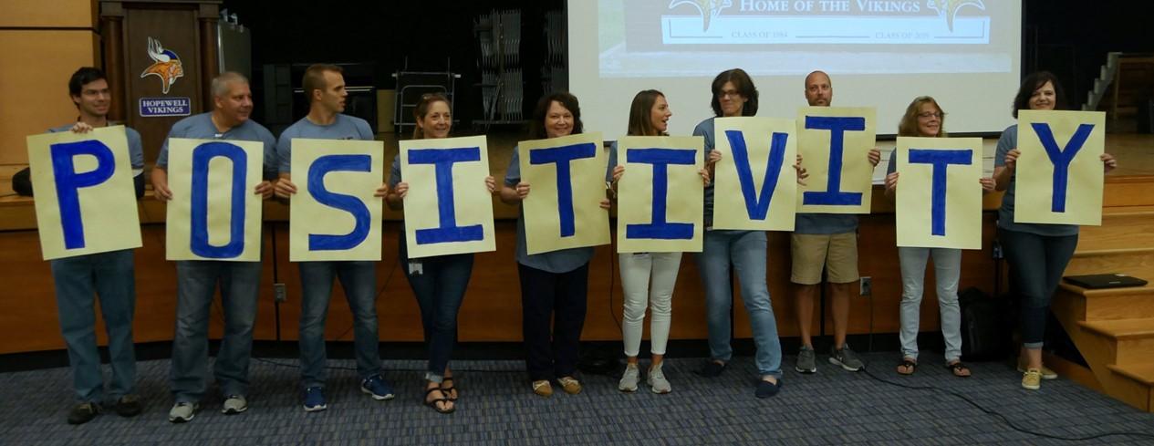 Teachers holding a positivity sign
