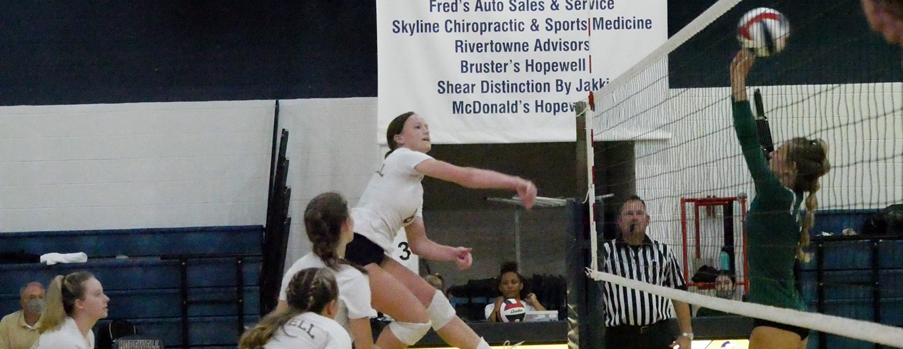 Girl's volleyball game. A player is spiking the ball.