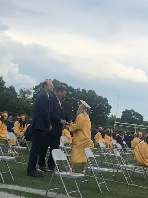 Principals shaking hands with graduate